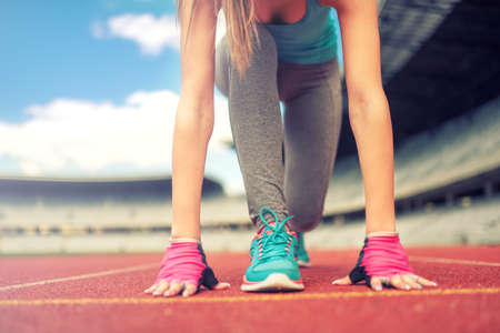 Athletic woman going for a jog or run at running track. Healthy fitness concept with active lifestyle.