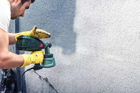 Photo pour Man painting a grey wall, renovating exterior walls of new house - image libre de droit