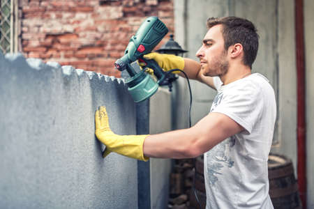 Photo pour Man using protective gloves painting a grey wall with spray paint gun. Young worker renovating house - image libre de droit