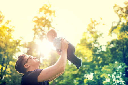 happy father holding little kid in arms, throwing baby in air. concept of happy family, vintage effect against light