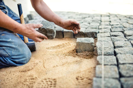 construction worker placing stone tiles in sand for pavement, terrace. Worker placing granite cobblestone pavement at local terrace