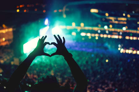 Heart shaped hands at concert, loving the artist and the festival. Music concert with lights and silhouette of a man enjoying the concert