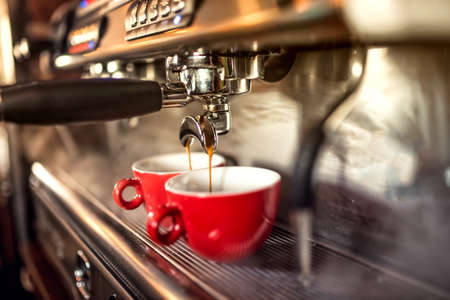 Photo pour coffee machine preparing fresh coffee and pouring into red cups at restaurant, bar or pub. - image libre de droit