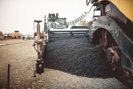 Foto de Paver machinery laying fresh asphalt or bitumen during road construction on building site. vintage, retro effect on photo - Imagen libre de derechos