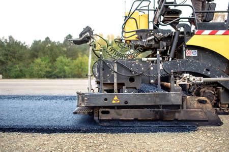 Foto de industrial pavement truck laying fresh asphalt on construction site, asphalting - Imagen libre de derechos