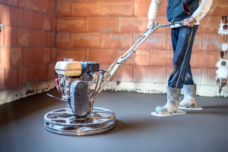 Worker with power trowel tool finishing concrete floor, smooth concrete surface at house construction