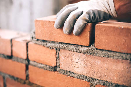 Photo pour Close up of industrial bricklayer installing bricks on construction site - image libre de droit