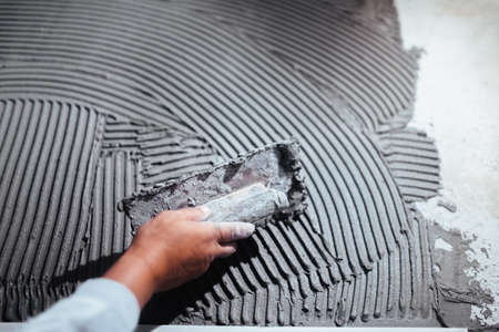 Photo pour close up of worker hand plastering a wall, adding adhesive with comb trowel - image libre de droit