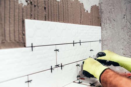 Photo for Renovation in progress. Industrial worker installing bathroom ceramic tiles - Royalty Free Image