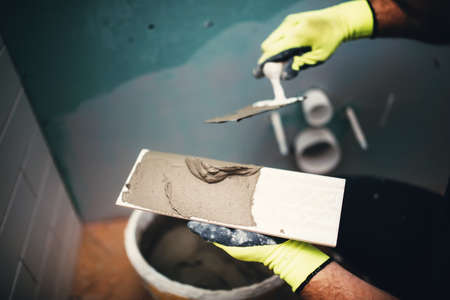 Photo pour industrial close up detail of worker adding cement adhesive on small ceramic tiles - image libre de droit