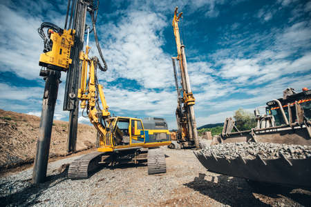 Photo pour Highway construction site with heavy duty machinery. Two Rotary drills, bulldozer and excavator working - image libre de droit