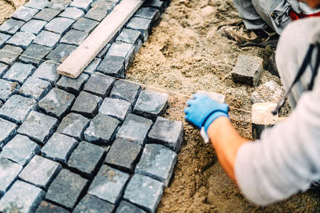 Construction worker details.Building of road or sidewalk with granite stone as pavement