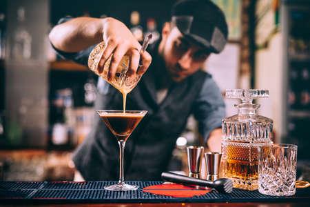 Photo pour Portrait of professional bartender preparing alcoholic drinks at bar - image libre de droit