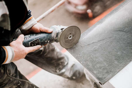 Photo for Construction site details - industrial tool, worker with angle grinder cutting marble stone - Royalty Free Image