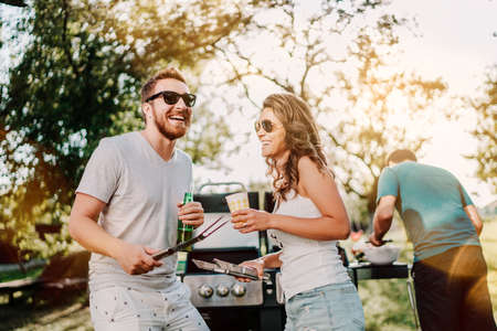 Photo for Group of smiling friends in vacation having beers and cooking on garden barbecue. Lifestyle, leisure concept - Royalty Free Image