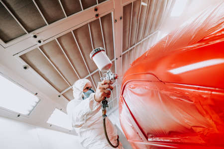 Photo pour automotive industry details - mechanic engineer using spray gun and painting a red car - image libre de droit
