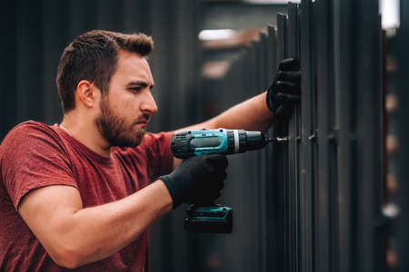 Foto de Portrait of construction worker installing metal elements using cordless screwdriver - Imagen libre de derechos