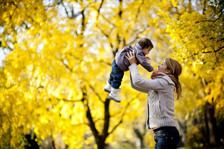 Mother and baby girl in the autumn forest