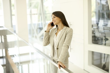 Foto de Young woman with mobile phone in the office - Imagen libre de derechos