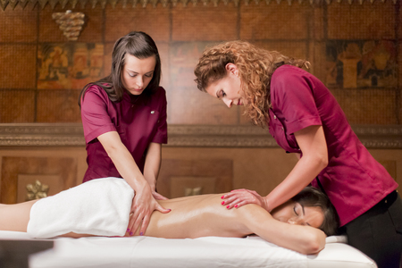 Photo for Two masseuses doing a massage with four hands - Royalty Free Image