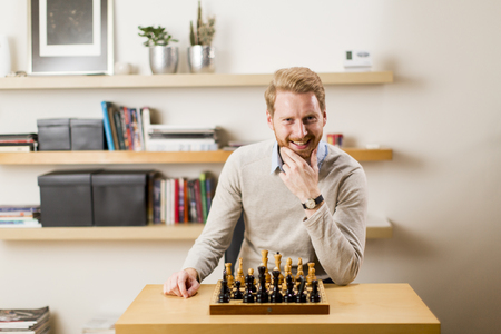 Portrait of a happy man playing chess at homme