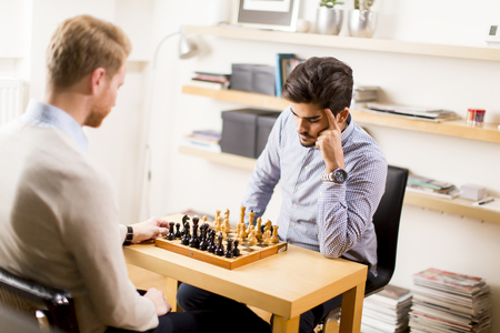 Portrait of a happy men playing chess at homme