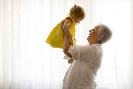 Photo pour Grandmother holding little granddaughter in the room at home - image libre de droit