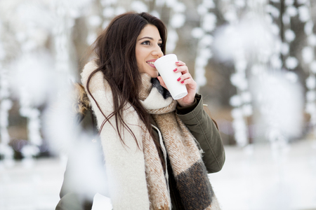 Photo pour Pretty young woman drinking hot tea on a cold winter day - image libre de droit