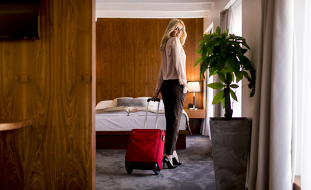 Young blond businesswoman arrives in a hotel room with red suitcase