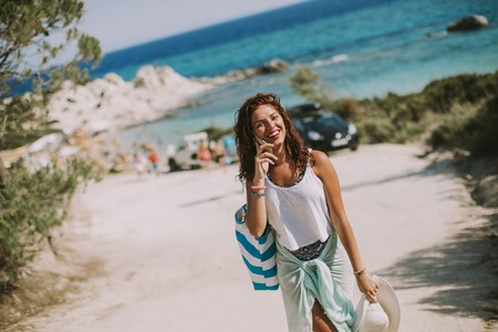 Foto de Pretty young woman with a bag using mobile phone on the beach at sunny summer day - Imagen libre de derechos