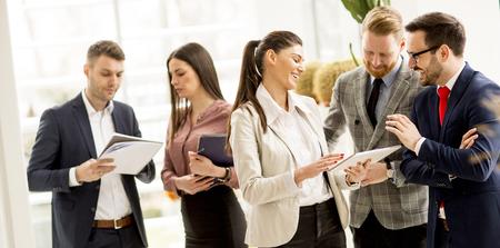 Foto de Meeting of group of businesspeople in the office standing in front of  large window in modern office - Imagen libre de derechos