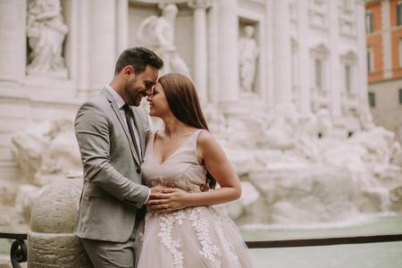 Foto de Just married bride and groom posing in front of Trevi Fountain (Fontana di Trevi), Rome, Italy - Imagen libre de derechos