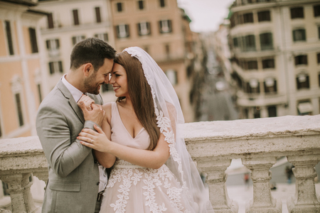 Foto de Young attractive newly married couple  posing in Rome with beautiful and ancient architecture in the background - Imagen libre de derechos