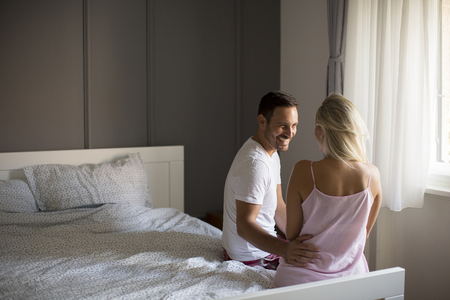 View at affectionate lovers embracing on bed at home