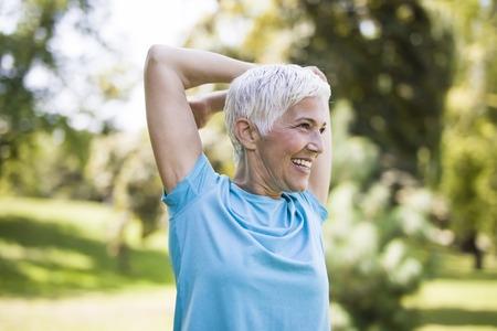 Foto de Portrait of senior woman doing exercise for stretching arms in the park - Imagen libre de derechos