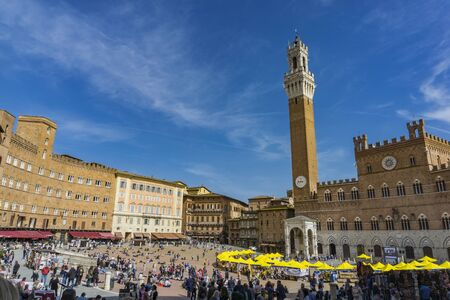 SIENA, ITALY - APRIL 8, 2018: Unidentified people at Piazza del Campo in Siena. It was built in 13th century and is regarded as one of Europe greatest medieval squares