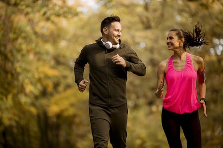 Foto de Young couple jogging together in autumn park - Imagen libre de derechos