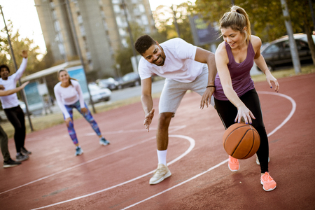 Photo pour Group of multiethnic young people  playing basketball on court - image libre de droit