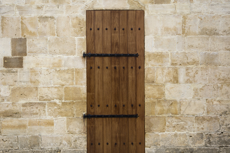 Foto de Ancient wooden door in old stone wall - Imagen libre de derechos