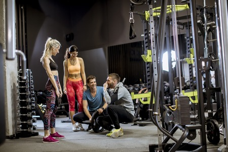 Photo for Group of young people in sportswear talking and laughing together while sitting on the floor of a gym after a workout - Royalty Free Image