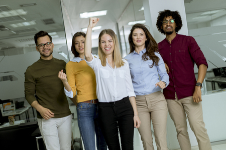 Portrait of group of young excited business people with hands up standing in office