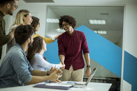 Photo for Group of young startup coworkers interacting around a table and handshaking in the office - Royalty Free Image