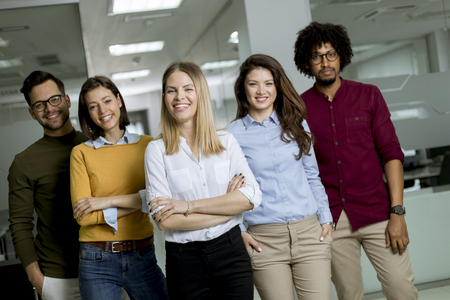 Photo pour Portrait of group of young excited business people standing in office - image libre de droit
