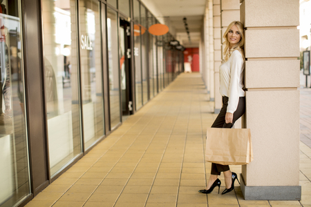 Photo pour Beautiful woman with paper shopping bag standing by the store - image libre de droit