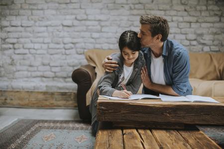 Foto de Happy family father and child daughter doing homework at home - Imagen libre de derechos
