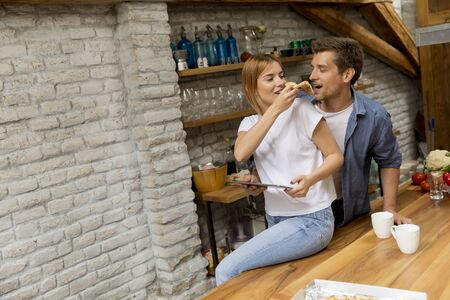 Photo for Lovely young couple eating pizza and using digital tablet by the table in the rustic apartment - Royalty Free Image