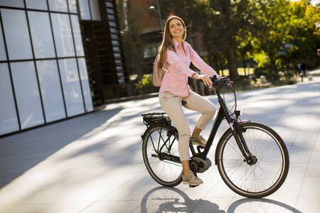 Foto de Young woman riding an electric bicycle in urban environment - Imagen libre de derechos