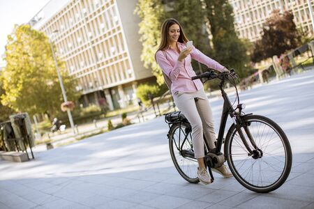 Photo pour Pretty young woman riding an electric bicycle and using mobile phone in urban environment - image libre de droit