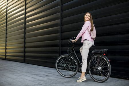 Photo pour Pretty young woman with modern city electric e-bike as clean sustainable urban transportation - image libre de droit