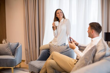 Photo pour Young couple drinking coffee and using digital tablet in the luxury contemporary apartment - image libre de droit